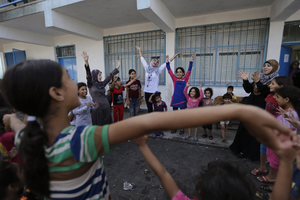 Photo - Volunteer Nisreen Shawa, 25, centre,  leads a play session with displaced Palestinian children at a U.N. school where they had sought refuge along with their families during the war, in Gaza City, Gaza Strip, Thursday, Aug. 7, 2014. Taking advantage of the continuing ceasefire, volunteers from the local non-profit NGO 'Tomooh' (Ambition), arranged a special play session for children to try and lessen the stress they've been enduring after the weeks of conflict. In the playground the children got a chance to sing and play group games under the caring eye of volunteers. They hope that their efforts will lessen the damage of the traumatic recent weeks events, or at least help them forget for a short while. (AP Photo/Lefteris Pitarakis)