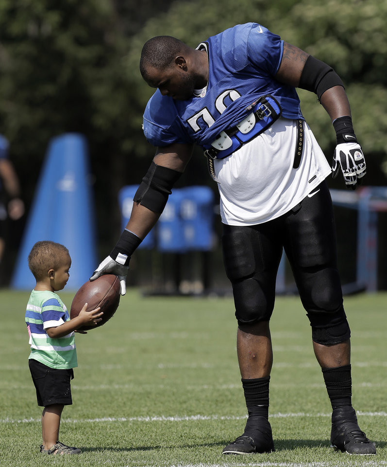 Detroit Lions tackle Corey Hilliard (OSU) hands his son Nyles, 1, a ball at the teams NFL football practice facility in Allen Park, Mich., Thursday, Aug. 1, 2013. (AP Photo/Paul Sancya) ORG XMIT: MIPS108