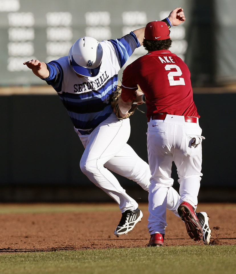 Photo - Oklahoma's Joshua Ake (2) tags out Seton Hall's Chris Selden (12) in the fifth inning during OU's season-opening college baseball game against Seton Hall at L. Dale Mitchell Park in Norman,  Okla., Friday, Feb. 14, 2014. Photo by Nate Billings, The Oklahoman