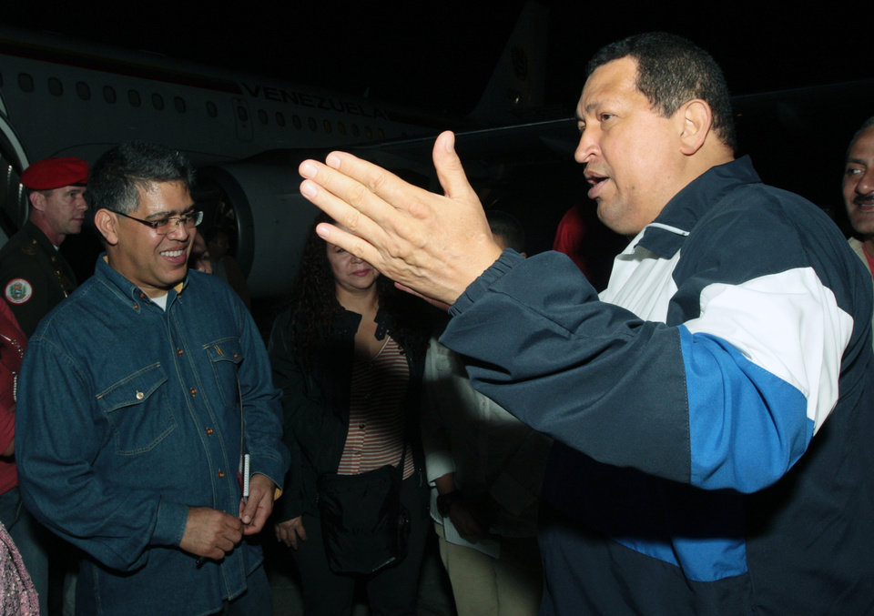 Photo -   In this photo released by Miraflores Press Office, Venezuela's President Hugo Chavez, right, speaks with Vice President Elias Jaua upon his arrival to the airport in Maiquetia near Caracas, Venezuela, Thursday, April 26, 2012. Chavez has returned home after 11 days in Cuba where he was undergoing radiation therapy treatment. (AP Photo/Miraflores Press Office, Efrain Gonzalez)