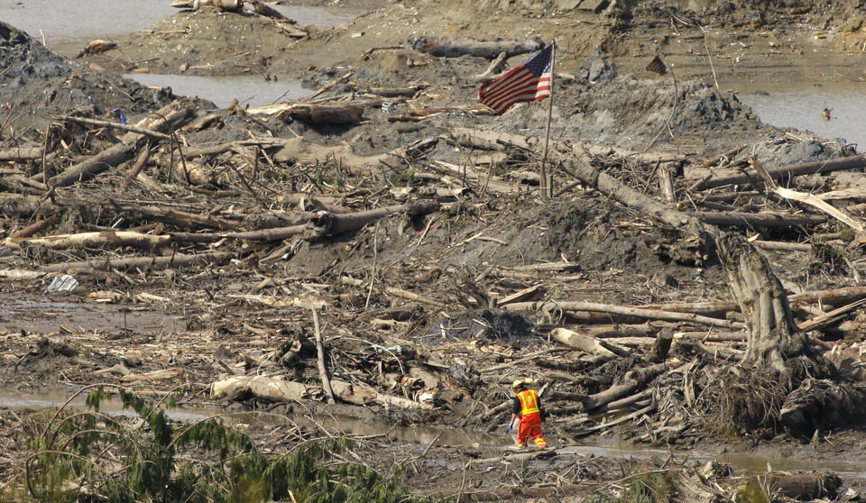 Photo - A searcher walks through a channel of water as a flag flies in the debris field Monday, March 31, 2014, near Darrington, Wash., at the site of the massive mudslide that hit the nearby community of Oso,Wash. on March 22, 2014. (AP Photo/Ted S. Warren)