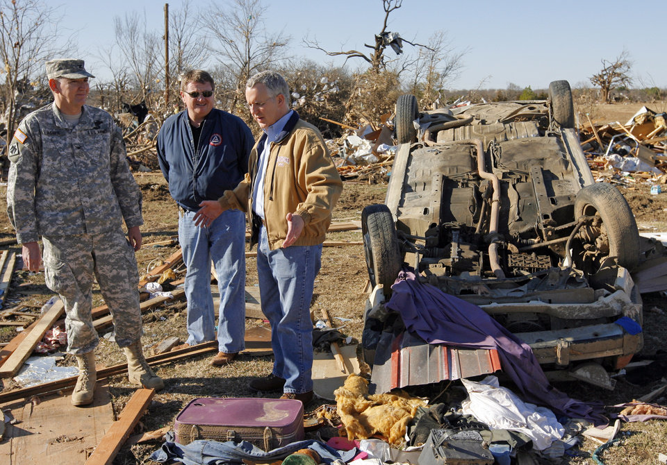 Photo - From left, Col. Robbie Asher, chief of staff for the Oklahoma National Guard, Albert Ashwood, director of the Oklahoma Department of of Emergency Management, and Gov. Brad Henry survey tornado damage at the Bar K Mobile Home Park in Lone Grove, Okla., Wednesday, February 11, 2009. On Tuesday, February 10, 2009, a tornado moved through Lone Grove killing at least eight people. BY NATE BILLINGS, THE OKLAHOMAN