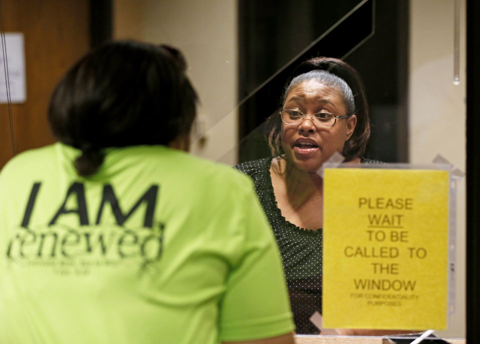 Naukeshia Johnson, right, helps Darlene Neal with questions Thursday at the Oklahoma County Human Services Center in Oklahoma City. Neal had questions about SoonerCare and joining the food stamp program SNAP because of a change in her husband's work. Photo by Nate Billings, The Oklahoman