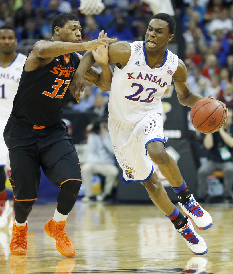 Photo - Kansas guard Andrew Wiggins (22) is covered by Oklahoma State guard Marcus Smart (33) during the second half of an NCAA college basketball game in the quarterfinals of the Big 12 Conference men's tournament in Kansas City, Mo., Thursday, March 13, 2014. Kansas defeated Oklahoma State 77-70 in overtime. (AP Photo/Orlin Wagner)