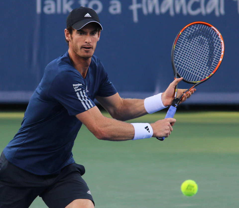Photo - Andy Murray, of Britain returns a volley to Roger Federer, of Switzerland, at the Western & Southern Open tennis tournament, Friday Aug. 15, 2014, in Mason, Ohio. (AP Photo/Tom Uhlman)
