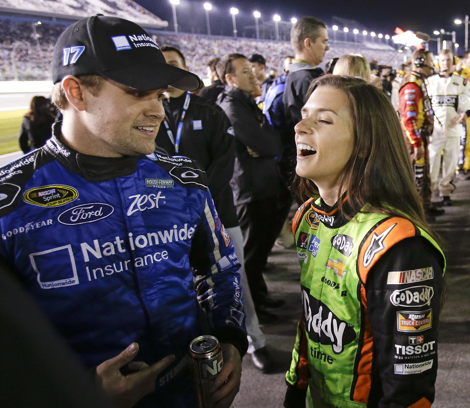 Photo - Drivers Ricky Stenhouse Jr., left, and Danica Patrick get together on pit road before the NASCAR Sprint Unlimited auto race at Daytona International Speedway in Daytona Beach, Fla., Saturday, Feb. 15, 2014. (AP Photo/John Raoux)