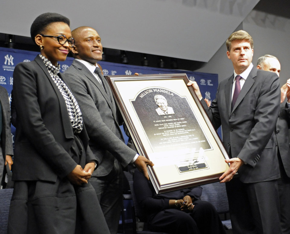 Photo - Zondwa Mandela, second from left, his wife Lindo Mandela, left, and New York Yankees owner Hal Steinbrenner, right, pose with a copy of the Nelson Mandela plaque before the Chicago Cubs and the Yankees play Game 2 of a baseball doubleheader on Wednesday, April 16, 2014, at Yankee Stadium in New York. Zondwa is Nelson's grandson. (AP Photo/Bill Kostroun)