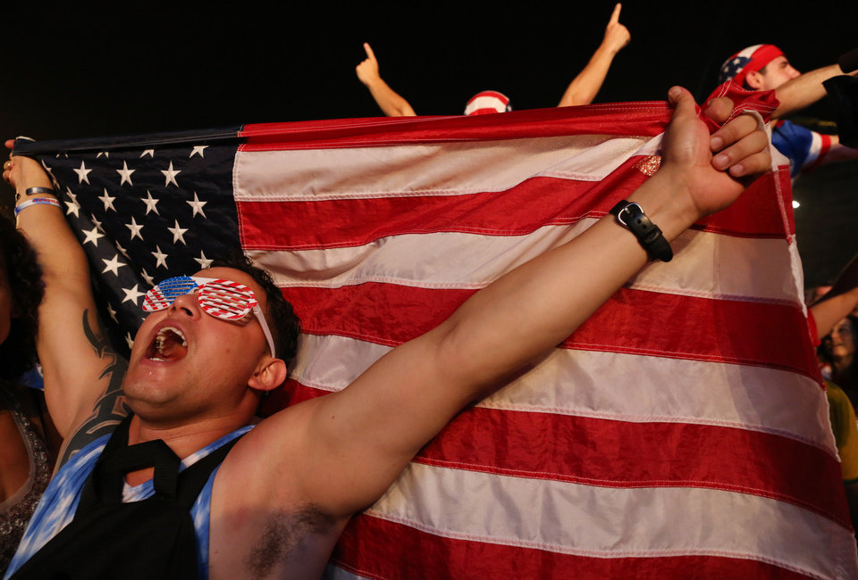 Photo - A soccer fan of the U.S. national soccer team celebrates his team's victory during a live broadcast of the soccer World Cup match between the Unites States and Ghana, inside the FIFA Fan Fest area on Copacabana beach, Rio de Janeiro, Brazil, Monday, June 16, 2014. Clint Dempsey scored in the first minute and rookie substitute John Brooks scored a late game winner as the U.S. defeated Ghana 2-1 in the World Cup opener for both. (AP Photo/Leo Correa)