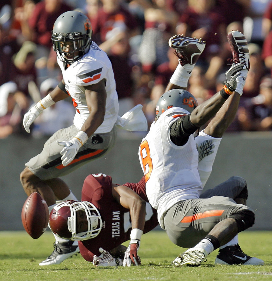 Texas A&M's Kenric McNeal (5) fumbles the ball after being upended by Oklahoma State's Daytawion Lowe (8) in front of Justin Gilbert (4) in the third quarter Saturday. The fumble and recovery turned the tide of the game, leading OSU to a 30-29 win in College Station, Texas. Photo by Nate Billings, The Oklahoman