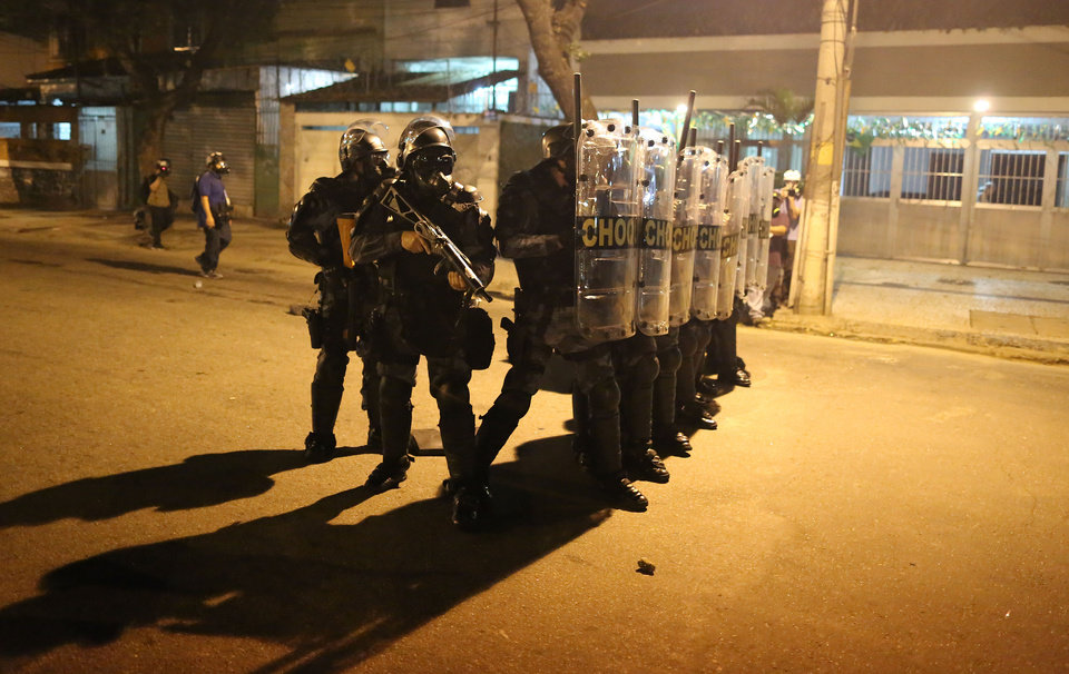 Photo - Police advance on anti-World Cup demonstrators protesting the money spent on the World Cup soccer tournament and demanding better public services near Maracana stadium in Rio de Janeiro, Brazil, Sunday, June 15, 2014. Police clashed with protesters marching toward the stadium ahead of the match between Argentina and Bosnia. (AP Photo/Leo Correa)