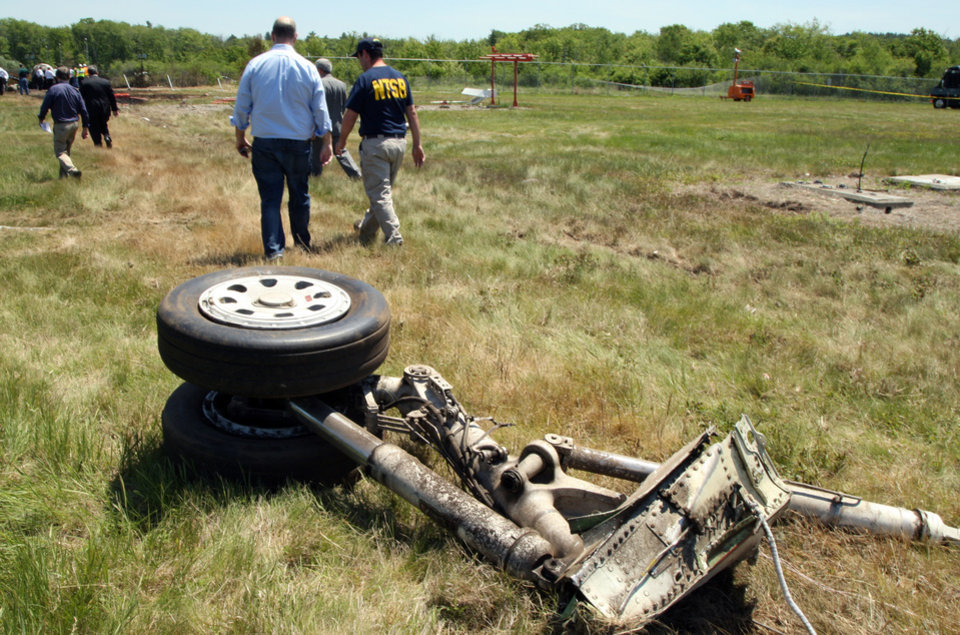 Photo - A National Transportation Safety Board official walks away from a piece of the landing gear at the scene Monday, June 2, 2014, in Bedford, Mass., where a plane plunged down an embankment and erupted in flames during a takeoff attempt at Hanscom Field on Saturday night. Lewis Katz, co-owner of The Philadelphia Inquirer, and six other people died in the crash. (AP Photo/Boston Herald, Mark Garfinkel, Pool)