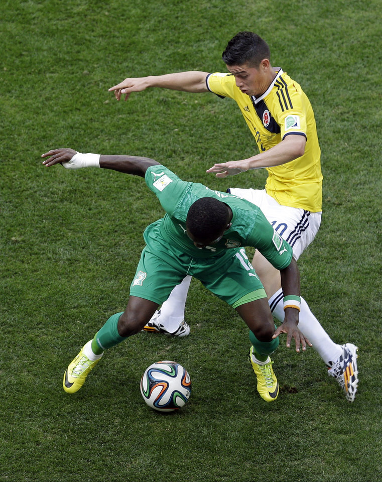 Photo - Colombia's James Rodriguez, right. and Ivory Coast's Max Gradel fight for the ball during the group C World Cup soccer match between Colombia and Ivory Coast at the Estadio Nacional in Brasilia, Brazil, Thursday, June 19, 2014.  (AP Photo/Themba Hadebe)