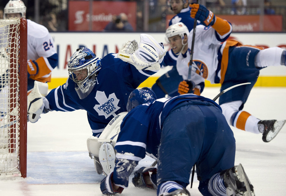 Photo - New York Islanders center John Tavares, right, flies through the air as his shot gets past Toronto Maple Leafs goaltender James Reimer and defenseman Jake Gardiner, foreground, during first-period NHL hockey game action in Toronto, Thursday, April 18, 2013. (AP Photo/The Canadian Press, Frank Gunn)