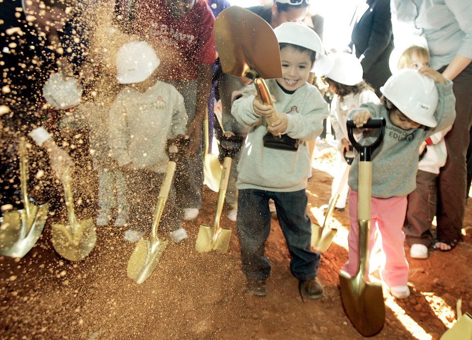 Photo - 3-year-old Isaac Guerrero throws dirt as he and his little sister 2-year-old Natalia Guerrero take part in the EDUCARE groundbreaking ceremony at Grand Boulevard and Byers Avenue in Oklahoma City, Okla. Monday Nov. 5, 2007. BY STEVE GOOCH, THE OKLAHOMAN ORG XMIT: KOD