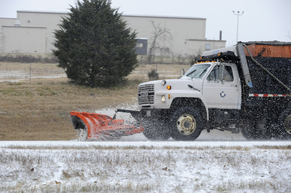 A snow plow clears snow and ice from U.S. Highway 62 in Mountain Home, Ark., Thursday, Dec. 5, 2013. A mixture of ice and snow fell in northern Arkansas Thursday. (AP Photo/The Baxter Bulletin, Kevin Pieper)
