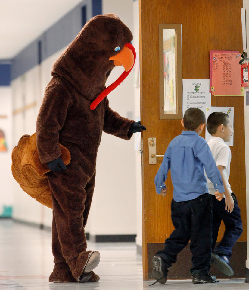 Photo - Children cheered and laughed and rushed to touch this 7 foot-tall turkey as he walked through the halls of Herronville Elementary School at SW 29 and McKinley Tuesday morning, Nov. 22, 2011. Inside the turkey suit was Leon Hill, a veteran educator who is serving his first year as principal at this south Oklahoma City Public School.Last month, Hill issued a reading challenge to his students, which range from pre-kindergarten through fifth grade.  He promised that if they would read at least 3,000 books, he would come to school dressed as a turkey before the Thanksgiving break.The students accepted the challenge and exceeded their goal,  reading a total of 4,444 books.  Hill credited the success of the reading challenge to the school's teachers and to the parents who either read with their children or encouraged them  to read.   Photo by Jim Beckel, The Oklahoman