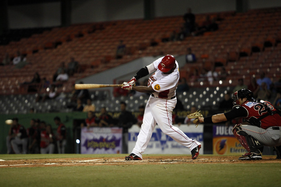 In this Dec. 29, 2012 photo, Criollos of Caguas� Carlos Rivera hits a ball during a baseball game against Leones of Ponce in Caguas, Puerto Rico. On an island where the name of Roberto Clemente is emblazoned on stadiums, streets and schools, the sport of baseball is poised to make a late-inning rally. In the past year, Major League Baseball reported the second-highest number of signings from Puerto Rico since the year 2000. (AP Photo/Ricardo Arduengo)