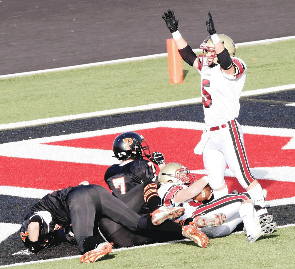 Photo - Lincoln Christian's Sam Doerner, top right, gives the touchdown signal after teammate Matt Lawwill scored during the third quarter.  Photo by CORY YOUNG, Tulsa World