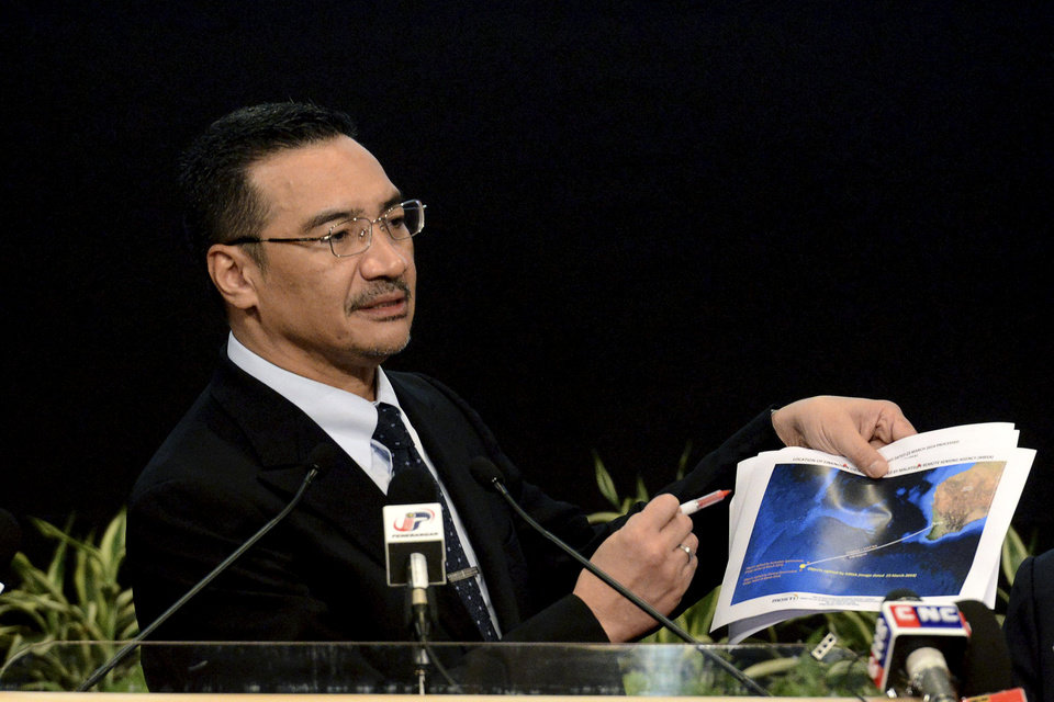 Photo - Malaysia's Defense Minister and acting Transport Minister Hishammuddin Hussein shows a printout of the latest satellite image of objects that might be from the missing Malaysia Airlines plane, at Putra World Trade Center in Kuala Lumpur, Malaysia, Wednesday, March 26, 2014. Hishammuddin said the objects were seen close to where three other satellites previously detected objects.  (AP Photo/Joshua Paul)