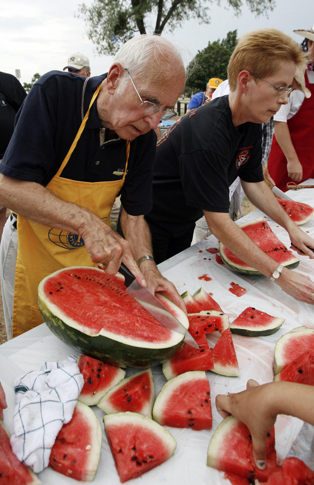 Bob Clarke and Lt. Cathy Davis carve free watermelon for the Kiwanis club's watermelon give-away during the Norman Independence Day Celebration at Reaves Park in Norman, Okla., on Saturday, July 4, 2009.     Photo by Steve Sisney, The Oklahoman