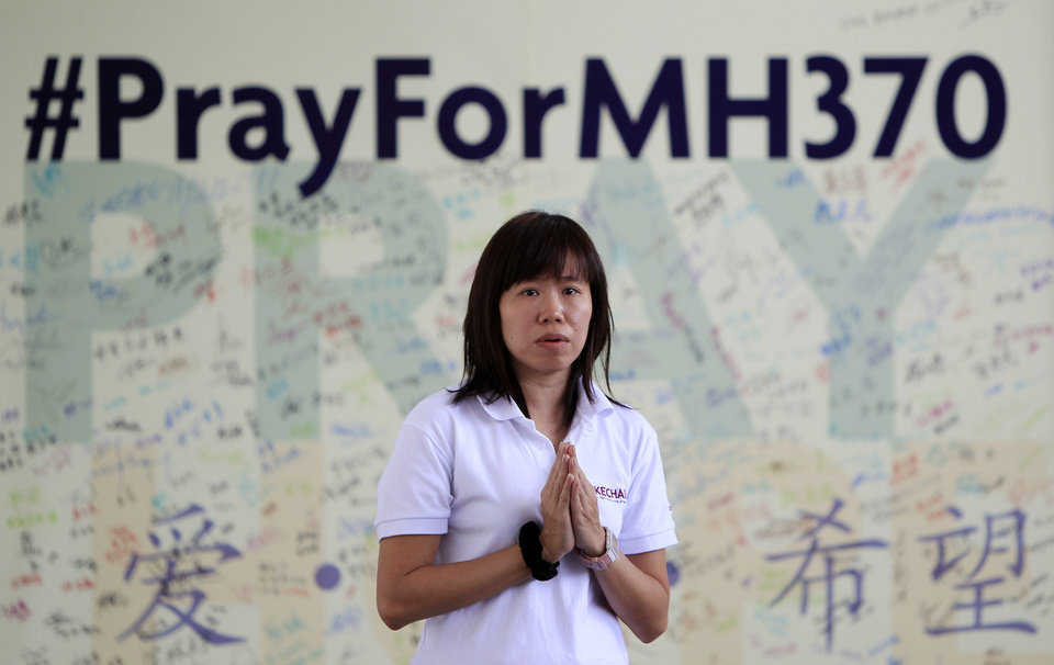 Photo - A member of Kechara Buddhist organization offers prayers for passengers onboard the missing Malaysia Airlines Flight 370 at Kechara Forest Retreat in Bentong, outside Kuala Lumpur, Malaysia, Sunday, April 13, 2014. After a week of optimism over four underwater signals believed to be coming from the missing Malaysian plane, the sea has gone quiet and Australia's leader is warning that the massive search will likely be long. (AP Photo/Lai Seng Sin)