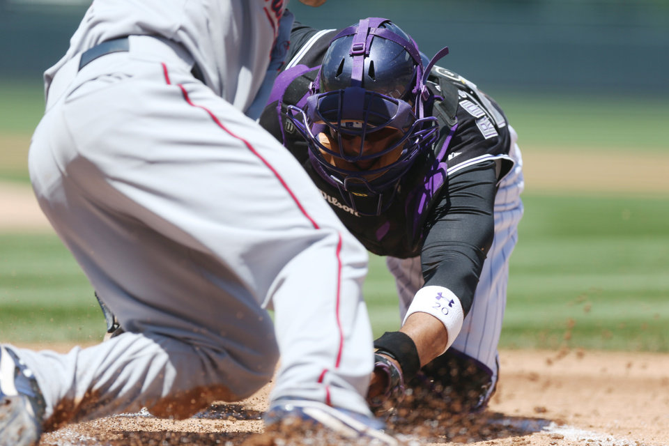 Photo - Colorado Rockies catcher Wilin Rosario, back, tags out Minnesota Twins' Brian Dozier at home plate on the back end of a double play hit into by Kendrys Morales in the first inning of an interleague baseball game in Denver on Sunday, July 13, 2014. (AP Photo/David Zalubowski)