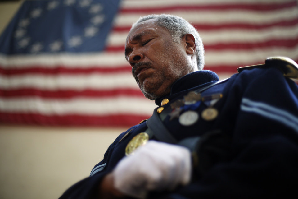 Photo - Civil War re-enactor Cpl. Robert Fuller Houston with the 3rd Regiment Infantry, lowers his head during a prayer at a ceremony Wednesday, Sept. 11, 2013, marking the 12th anniversary of the 9/11 terrorist attacks at the Betsy Ross House in Philadelphia. (AP Photo/Matt Rourke)