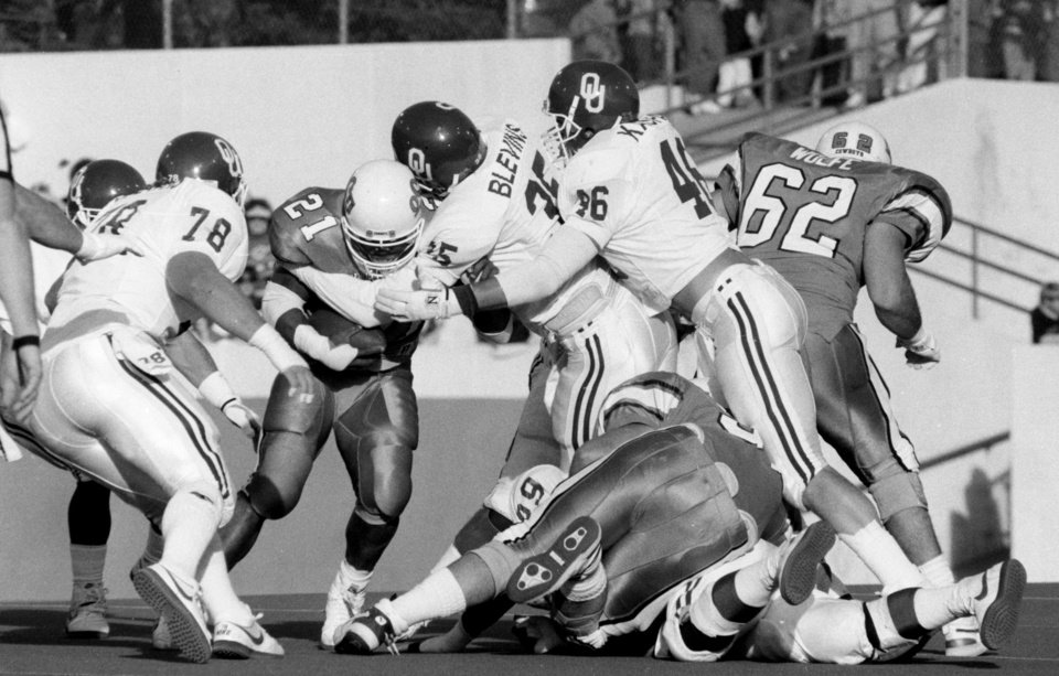 Photo - OU defense of Frank Blevins (35), Kert Kaspar (46) and Scott Evans (78) stops OSU RB Barry Sanders (21) during the University of Oklahoma (OU) at Oklahoma State University (OSU) Bedlam college football in Stillwater, Nov. 5, 1988. PHOTO BY JIM ARGO THE OKLAHOMAN. ORG XMIT: KOD