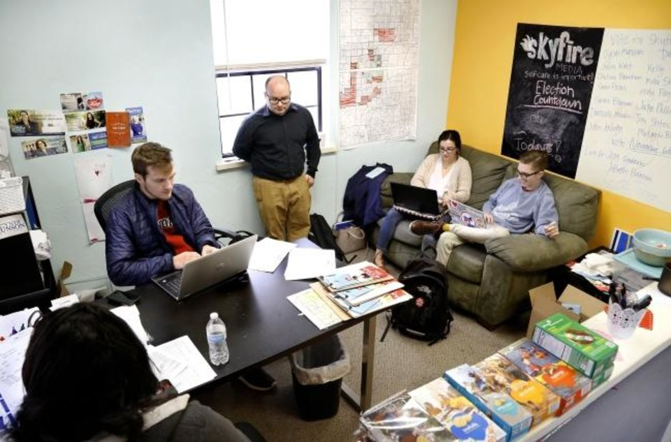 Photo -  Workers at Skyfire Media gather Friday in the company's reception area to check messages and social media sites. [Jim Beckel/The Oklahoman]
