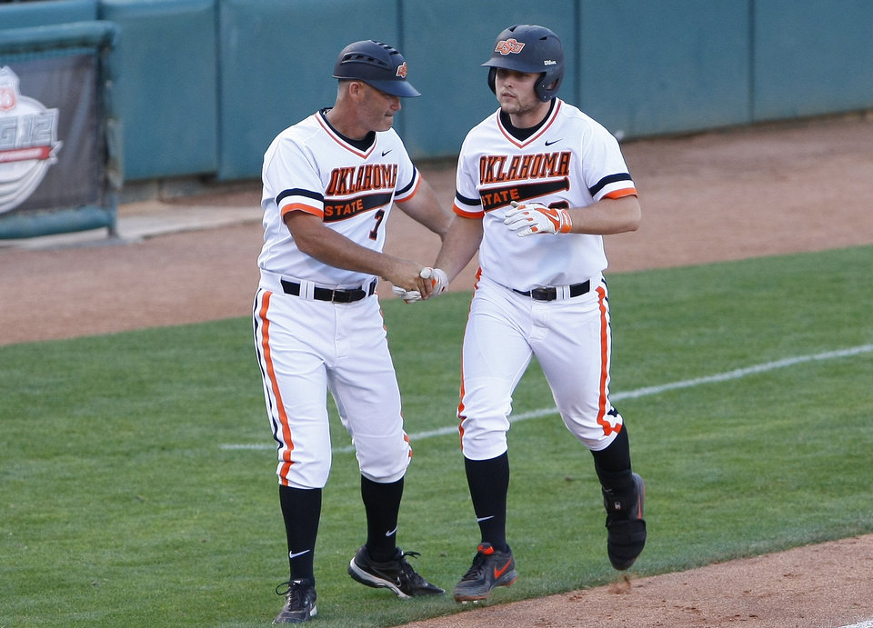 Photo - Oklahoma State's third base coach shakes Oklahoma State's Zach Fish, right, hand on his way to home after hitting a grand slam in the bottom of the sixth inning of a first-round game against Oklahoma in the Big 12 conference NCAA college baseball tournament in Oklahoma City, Wednesday, May 21, 2014. (AP Photo/Alonzo Adams)