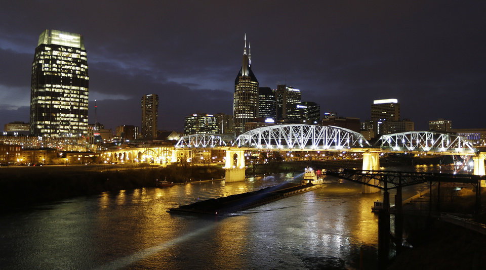 Photo - This Jan. 15, 2014 photo shows the Shelby Street pedestrian bridge spanning the Cumberland River in Nashville, Tenn. The banks of the Cumberland River in downtown Nashville are more than a place to watch barges pass. The bridge is one of the best viewpoints for the Nashville skyline that inspired Bob Dylan to write a country album. (AP Photo/Mark Humphrey)