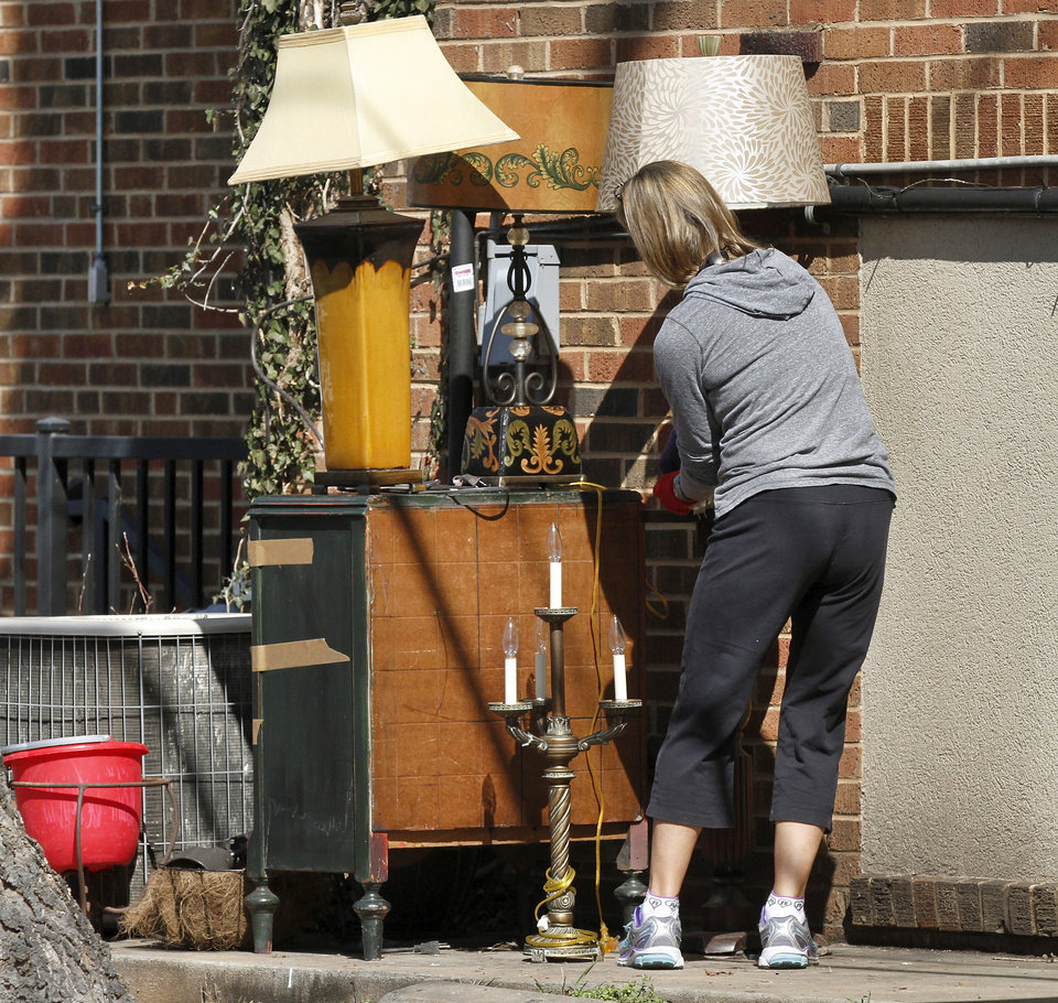 Photo - A woman carries lamps from the rear of the fraternity house and places them other furniture waiting to be loaded into trucks. Parents, friends and fellow students helped members of the SAE  fraternity remove all furniture and personal belongings from the house Tuesday afternoon, March 10, 2015. University officials closed the house and ordered it to be vacated by Tuesday night after a video showing students affiliated with the fraternity uttering offensive racial slurs during a weekend outing.      Photo by Jim Beckel, The Oklahoman