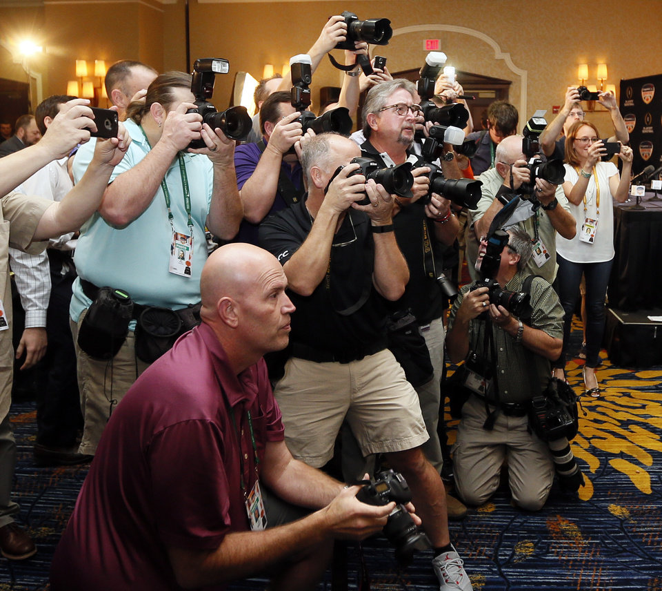 Photo - Photographers crowd together to take pictures of coaches during a news conference for the Capital One Orange Bowl, a College Football Playoff Semifinal game, at the Renaissance Fort Lauderdale Cruise Port Hotel in Fort Lauderdale, Florida, Wednesday, Dec. 30, 2015. The Oklahoma Sooners will play the Clemson Tigers on News Year's Eve. Photo by Nate Billings, The Oklahoman