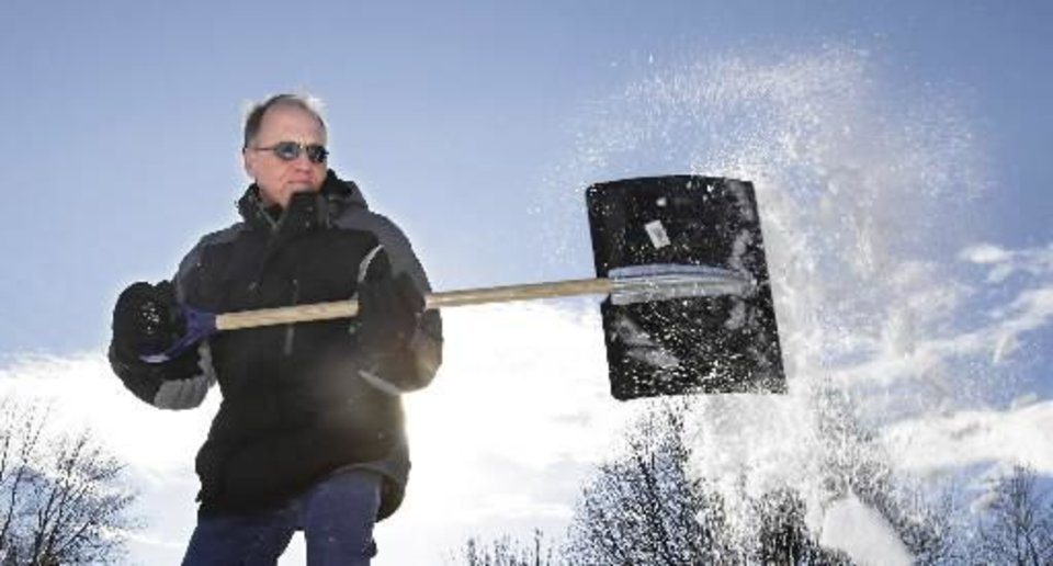Photo - John Judy shovels the snow from his in-laws driveway in Edmond, Thursday, February 3, 2011. Photo by David McDaniel