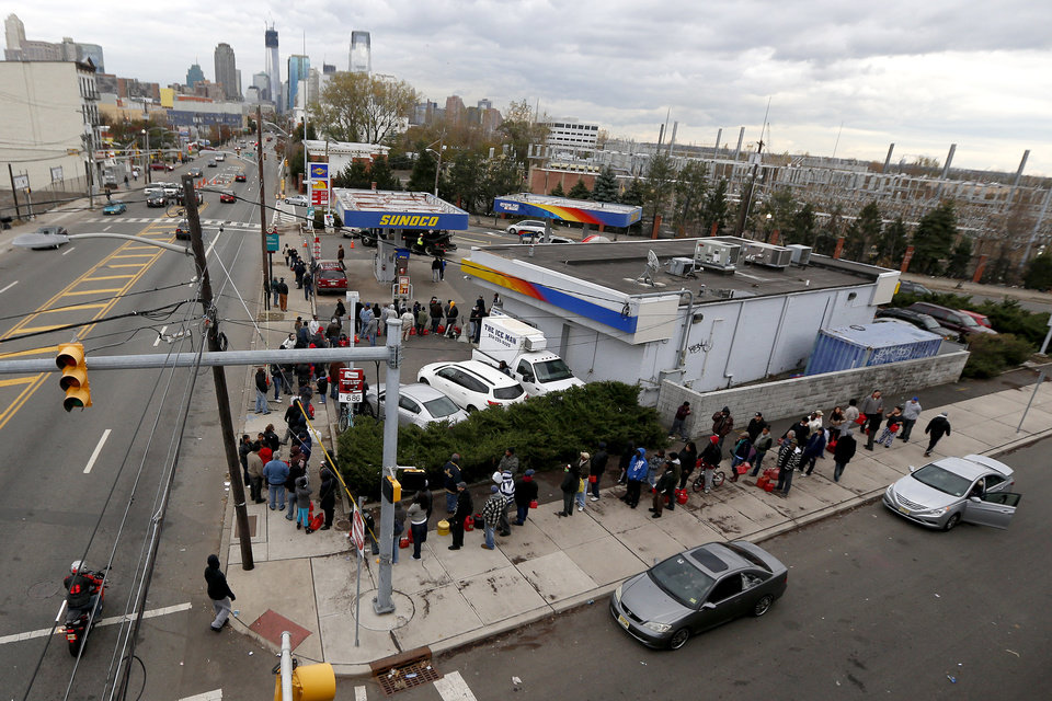 CORRECTS CITY TO JERSEY CITY INSTEAD OF HOBOKEN - With the New York and Jersey City skylines at the distance, including One World Trade Center, people wrap around the corner of a gas station waiting to fill containers, Friday, Nov. 2, 2012, in Jersey City, N.J. In parts of New York and New Jersey, drivers lined up Friday for hours at gas stations that were struggling to stay supplied. The power outages and flooding caused by Superstorm Sandy have forced many gas stations to close and disrupted the flow of fuel from refineries to those stations that are open. (AP Photo/Julio Cortez) ORG XMIT: NJJC120