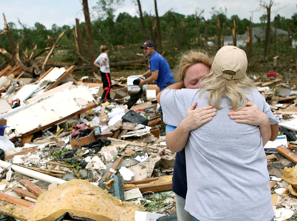 Photo - Standing in the middle of her destroyed home, Shelley Heston Bolles gets a hug from a family member in Little Axe, Oklahoma on Tuesday, May 11, 2010. By John Clanton, The Oklahoman