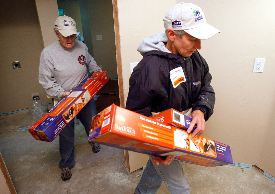 Photo - Betsy Baker with Marriott and Danna Korak with NCED (postal training center) move materials in preparation for floor work on a Habitat for Humanity house at 313 East Himes Street in Norman, Okla. on May 2, 2009.  Photo by Steve Sisney, The Oklahoman