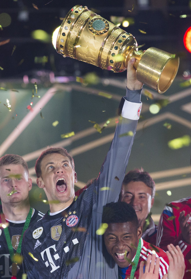Photo - Bayern goalkeeper Manuel Neuer lifts the trophy after winning the German Soccer Cup Final between FC Bayern Munich and Borussia Dortmund at the Olympic Stadium in Berlin, Germany, Saturday, May 17, 2014. (AP Photo/Gero Breloer)