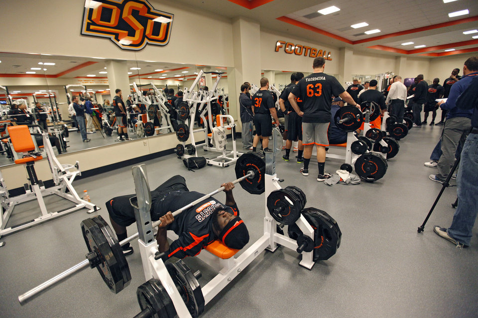 Photo - Lucien Antoine warms up on his bench press before lifting for the NFL scouts during the NFL pro day at Oklahoma State University on Wednesday, March 9, 2011, in Stillwater, Okla.  Photo by Chris Landsberger, The Oklahoman