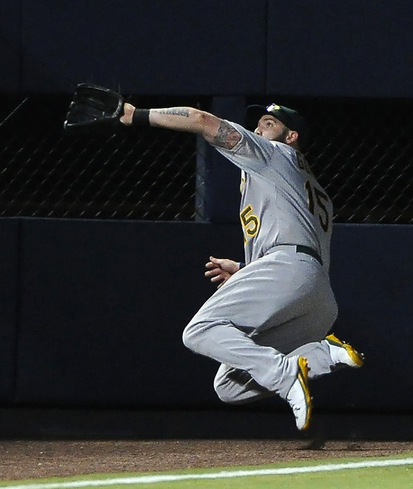 Photo - Oakland Athletics left fielder Jonny Gomes jumps to field the pop out in foul territory by Atlanta Braves' Jason Heyward during the first inning of a baseball game Sunday, Aug. 17, 2014, in Atlanta. (AP Photo/David Tulis)