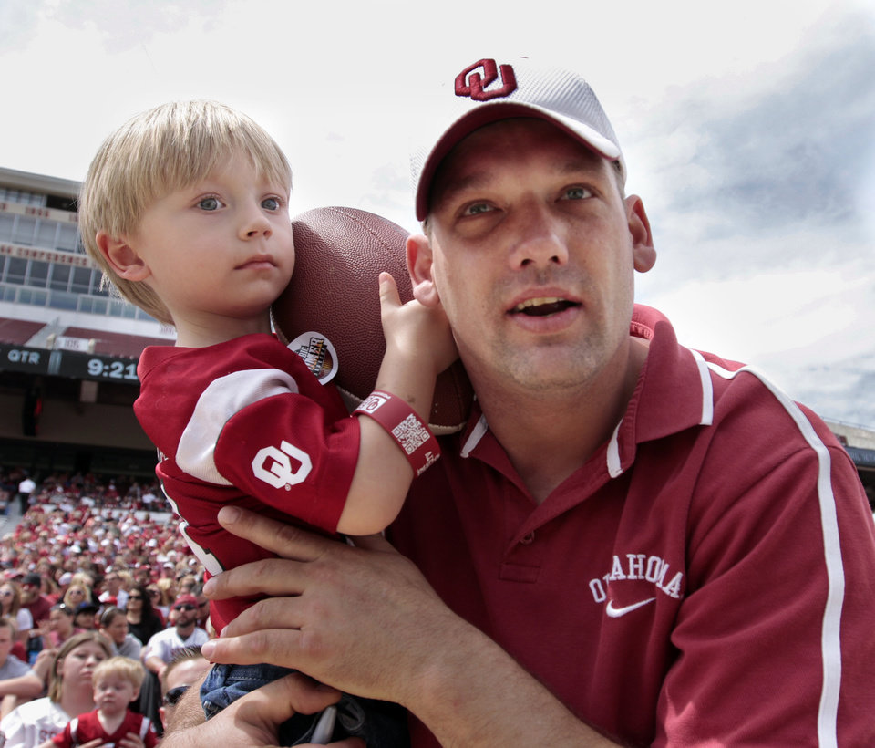 Randy Traw carries three-year-old son Danny to the front of the stadium hoping for autographs before the annual Spring Football Game at Gaylord Family-Oklahoma Memorial Stadium in Norman, Okla., on Saturday, April 13, 2013. Photo by Steve Sisney, The Oklahoman