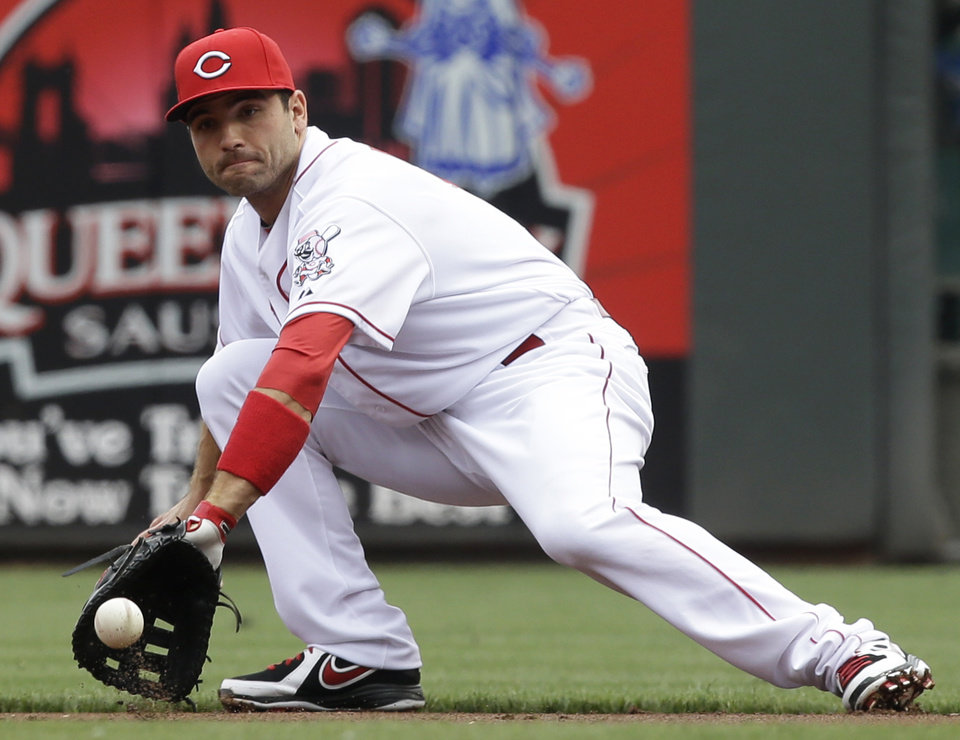 Photo - Cincinnati Reds first baseman Joey Votto fields a ground ball hit by Chicago Cubs' David DeJesus in the first inning of a baseball game on Saturday, May 25, 2013, in Cincinnati. Votto threw out DeJesus at first. (AP Photo/Al Behrman)