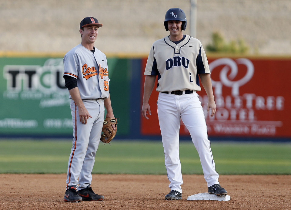 Photo - OSU's Donnie Walton (left) chats with ORU baserunner Joey Migliaccio during the OSU-ORU baseball game at J.L. Johnson Stadium, on Tuesday, April 22, 2014. CORY YOUNG/Tulsa World