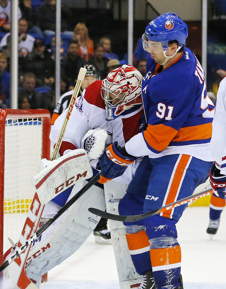 New York Islanders center John Tavares (91) checks Montreal Canadiens goalie Carey Price (31) during the second period of an NHL hockey game at the Nassau Coliseum in Uniondale, N.Y., Tuesday, March 5, 2013. Tavares received a penalty for goaltender interference. (AP Photo/Paul J. Bereswill)