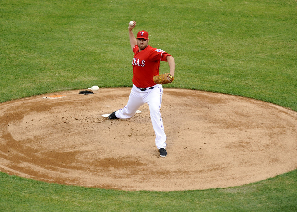 Photo - Texas Rangers starting pitcher Colby Lewis throws in the first inning of a baseball game against the Chicago White Sox, Saturday, April 19, 2014, in Arlington, Texas. (AP Photo/Matt Strasen)