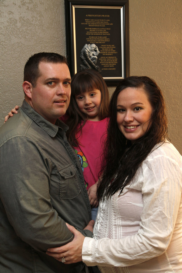 Photo - Josh Morgan, a firefighter recently let go from the Bethany Fire Department, stands Saturday with his wife Kristen and 5-year-old daughter Kaylee beside a firefighter's plaque in their home.  Photo by Paul Hellstern, The Oklahoman  PAUL HELLSTERN