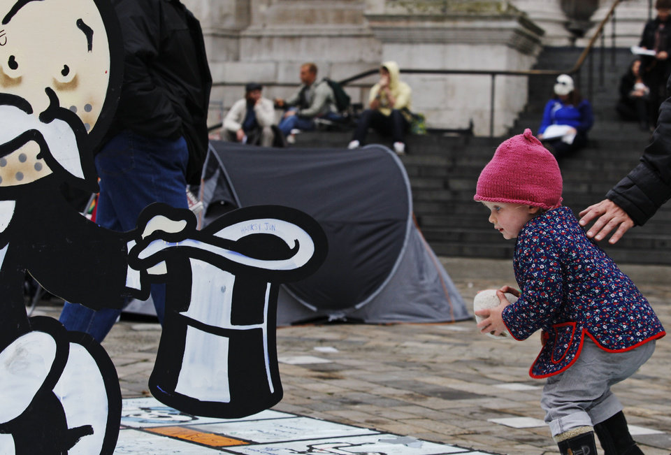 A baby girl plays near the 'Banker' character of a big-scale Monopoly game set up  at the anti-corporate protest tent camp outside St Paul's Cathedral, in central London, Thursday, Nov. 3, 2011. Asian stock markets fell Thursday for the fourth straight day as a European deal to bail Greece out of its financial mess appeared to be on the verge of unraveling. Greece's prime minister unexpectedly announced Monday that he would call a national vote on the European bailout plan that entails painful tax increases and drastic welfare cuts in exchange for massive aid to keep his debt-ridden nation solvent. (AP Photo/Lefteris Pitarakis) ORG XMIT: LLP108