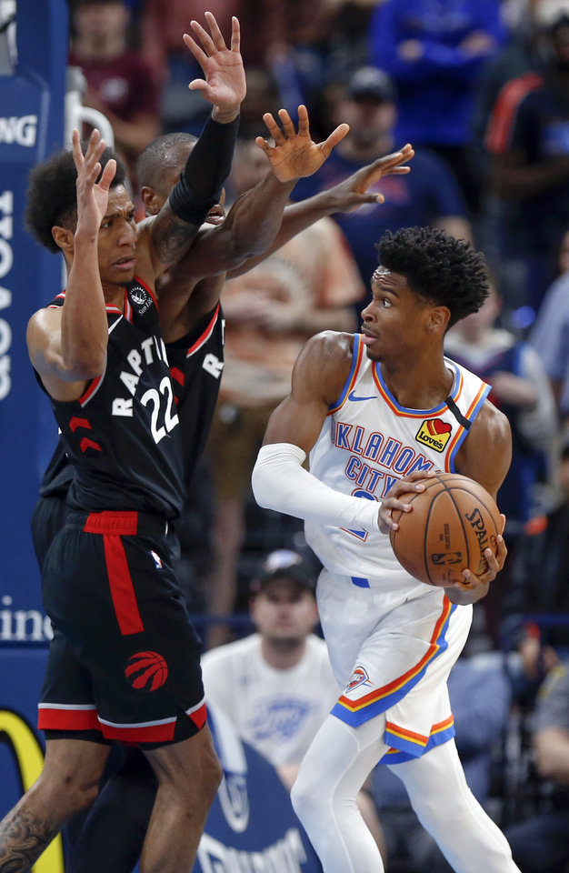 Photo - Oklahoma City's Shai Gilgeous-Alexander (2) looks to pass around Toronto's Patrick McCaw (22), left, and Serge Ibaka (9) in the third quarter during an NBA basketball between the Oklahoma City Thunder and the Toronto Raptors at Chesapeake Energy Arena in Oklahoma City, Wednesday, Jan. 15, 2020. Toronto won 130-121. [Nate Billings/The Oklahoman]
