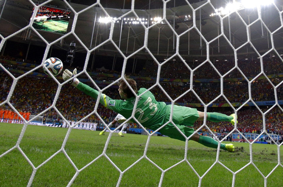 Photo - Netherlands' goalkeeper Tim Krul makes a save on a shot by Costa Rica's Michael Umana during a penalty shootout in extra time during the World Cup quarterfinal soccer match at the Arena Fonte Nova in Salvador, Brazil, Saturday, July 5, 2014. The Netherlands defeated Costa Rica 4-3 in penalties after a 0-0 tie. (AP Photo/Wong Maye-E)
