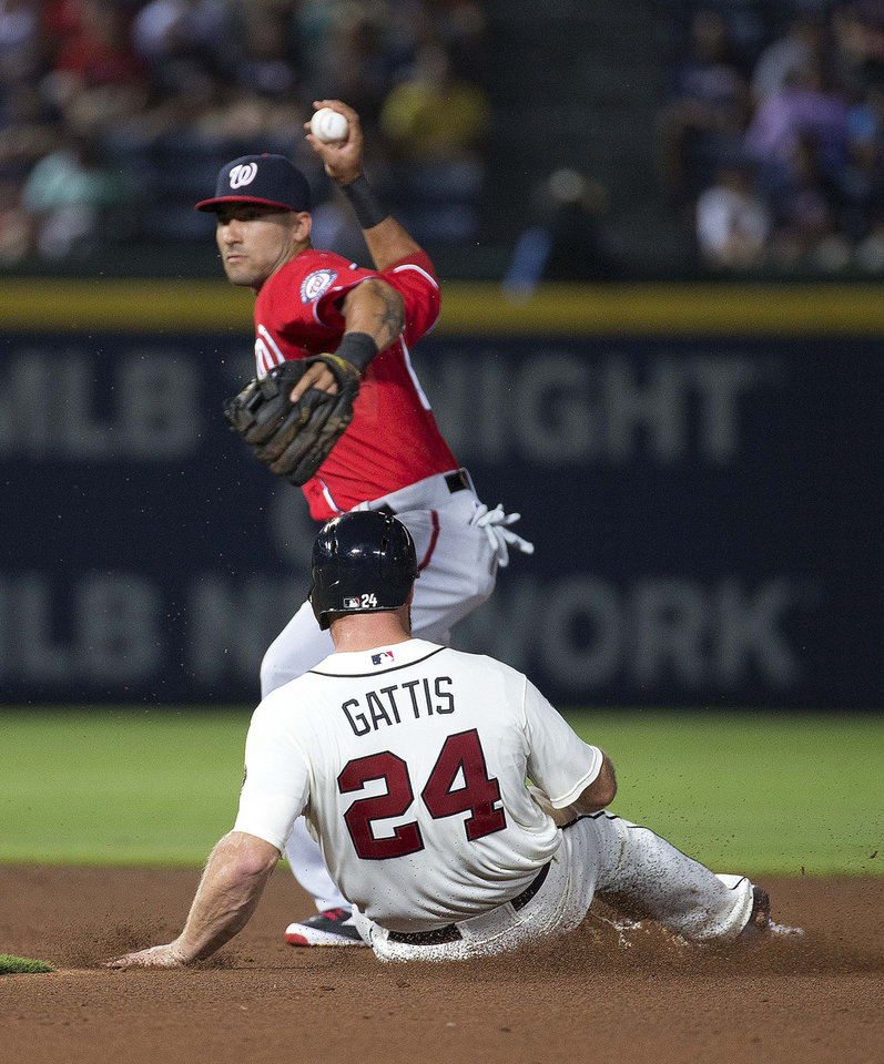 Photo - Washington Nationals shortstop Ian Desmond forces out Atlanta Braves' Evan Gattis (24) as he turns a double play on a Chris Johnson ground ball in the third inning of a baseball game Saturday, Aug. 9, 2014, in Atlanta. (AP Photo/John Bazemore)